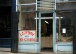 Display window with a sign saying Laundry and Dry Cleaners and a few plants - copyright Romy Ashby