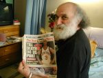 """Ira Cohen holding up a newspaper with the headline """"TILL DEATH DO US PART"""" - copyright Romy Ashby"""