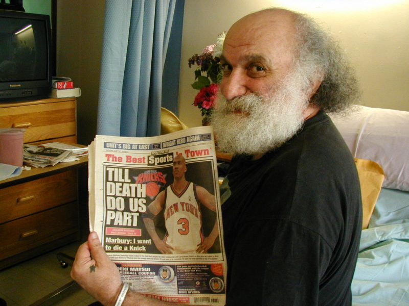 "Ira Cohen holding up a newspaper with the headline ""TILL DEATH DO US PART"" - copyright Romy Ashby"