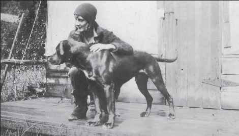 A woman called Pete with a woolen hat on kneeling next to a big dog